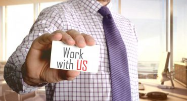 Work with us. Businessman holding a card with a message text wri